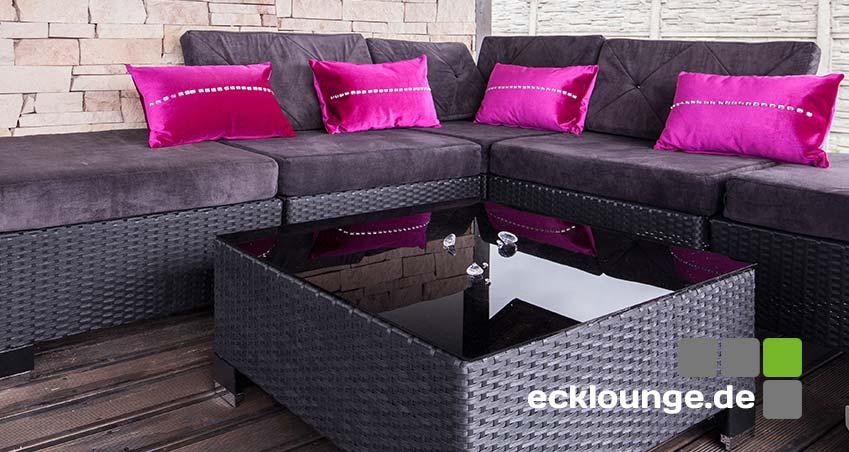 Eine Ecklounge anthrazot mit rosa Kissen. Dvor ein anthrazitfarbener Gartentisch aus Rattan mit einer schwarzen Glasplatte