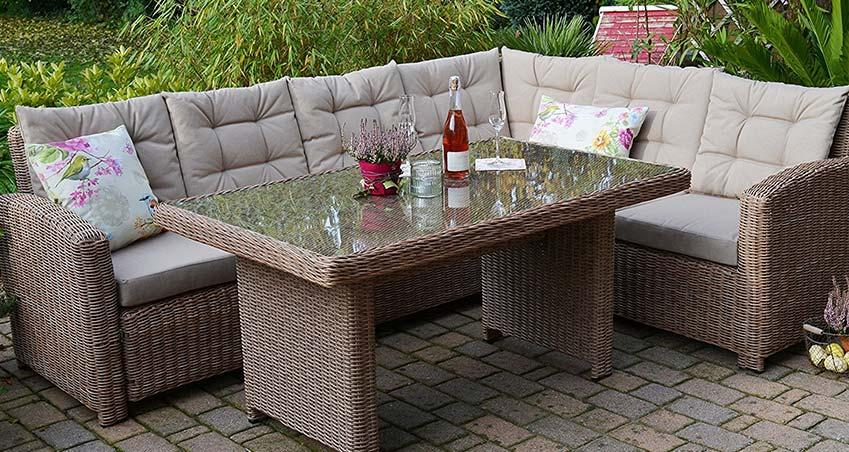 EIne naturfarbene Ecklounge mit dekoration und hohem Tisch in einem Garten