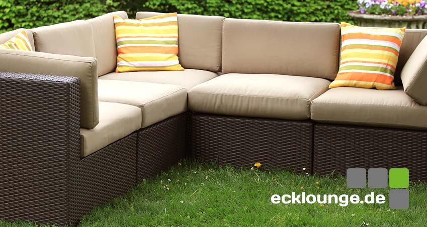 Eine Ecklounge / Gartenlounge ohne Tisch im Garten auf Grass vor einer Hecke