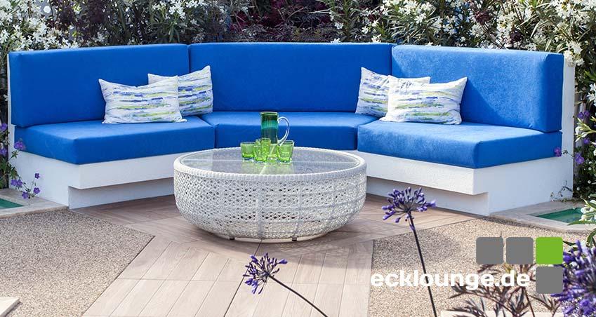 weiße Ecklounge mit blauen Polstern und Kissen in Garten mit lila Blumen
