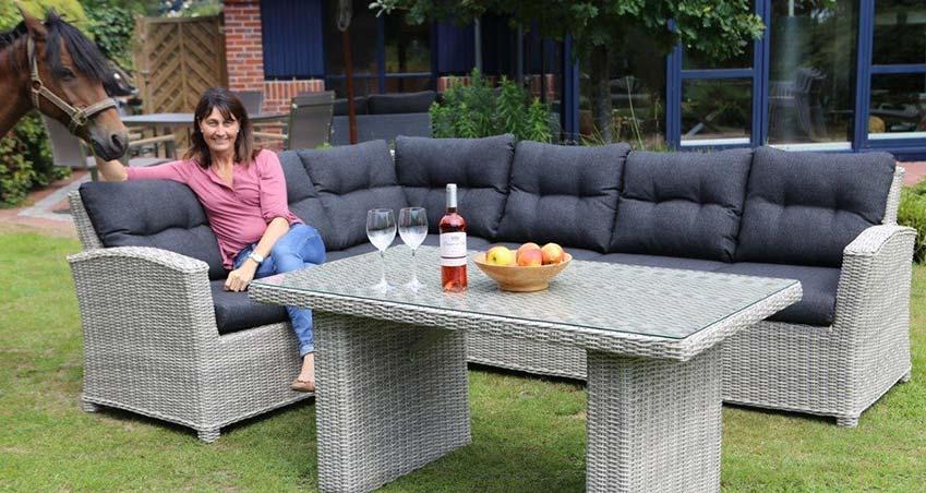Ecklounge von Destiny im Garten vor dem Haus. Auf der Ecklounge sintzt eine Frau mit rosa Bluse und blauer Jeans und trinkt Wein. Neben ihr steht ein braunes Pferd, von dem man den Kopf im Bild sehen kann.